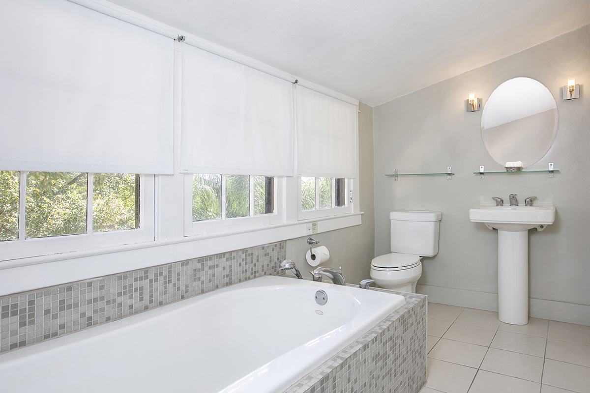 Vanilla Room Bath with large soaking tub, modern toilet and sink, mirror and shelves, large windows